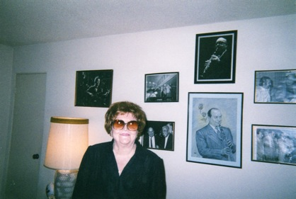 With a large potrait of Barney over her head, to the right
