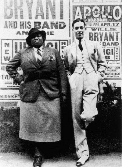 American blues singer Gladys Bentley (1907 - 1960) poses with bandleader Willie Bryant (1908 - 1964) outside the Apollo Theater where posters advertise a performance by Bryant & his band, New York, New York, April 17, 1936. (Photo by Frank Driggs Collection/Getty IMages)